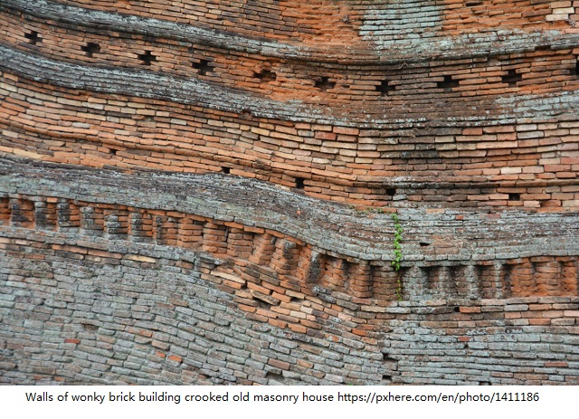 Walls of wonky brick building crooked old masonry house